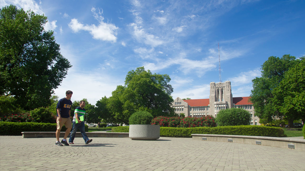 Two UE students walking in the front oval on campus in Summer.
