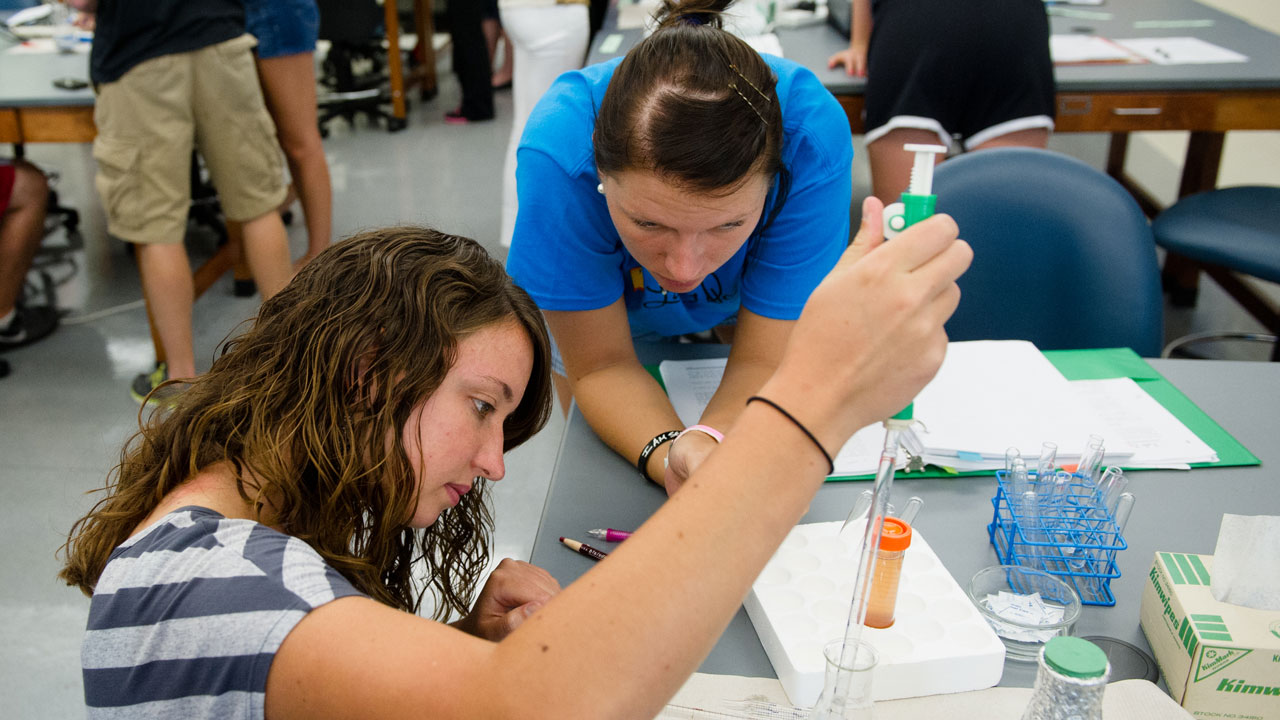 UE students in the lab with test tubes.