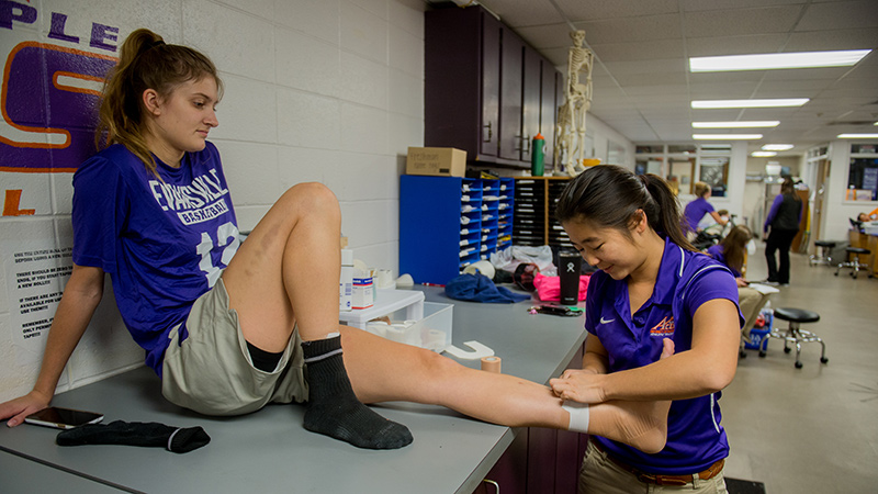 Two female athletic traning students wrapping the ankles of female athletes.