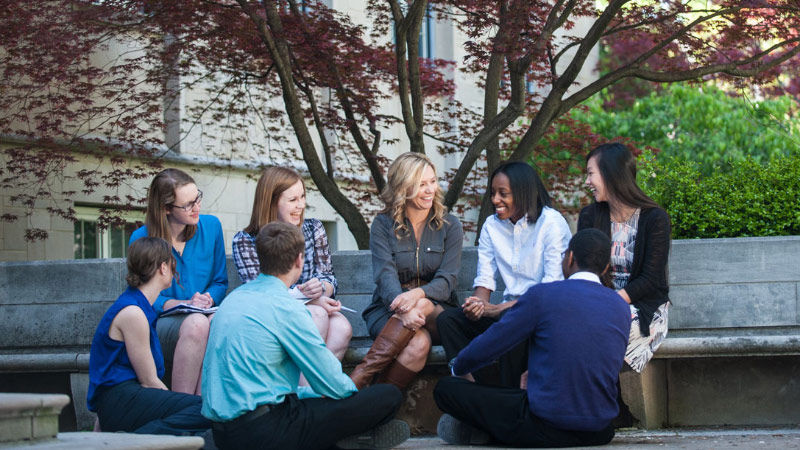 Group of students and faculty of different races and genders having a lively, friendly converstation with each other outside on the campus grounds.