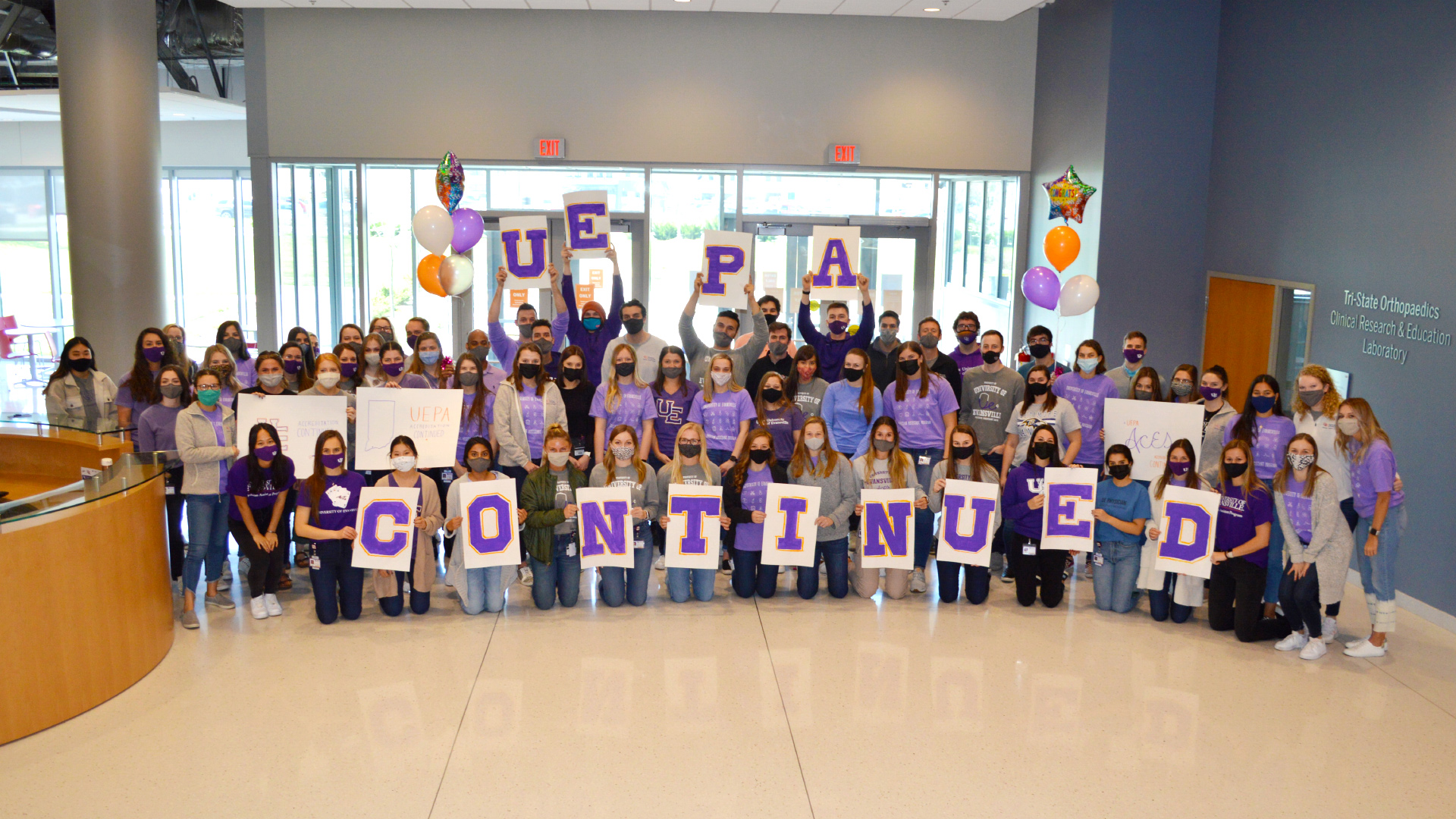 UE PA students holding up 'UE PA Continued' signs.