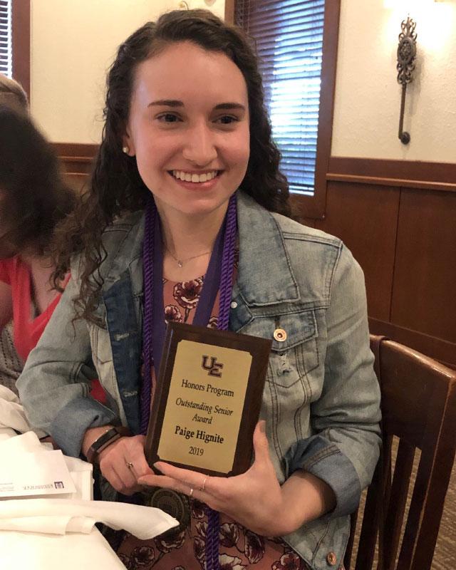 Paige Hignite holding award