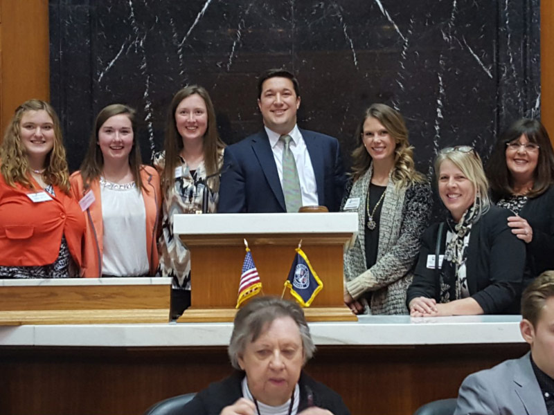 UE education students Sara Cannaday, Megan Hawkins, and Heather Dougan standing with others at the Indiana Statehouse podium.
