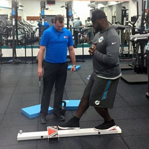 Kyle Matsel assiting Miami Dolphins player in gym