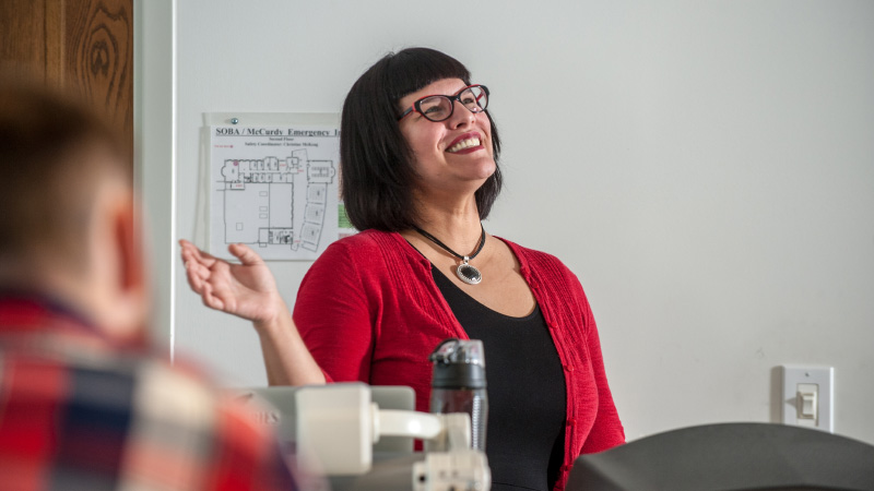 Lisa Nikolidakis giving a lecture with a smile