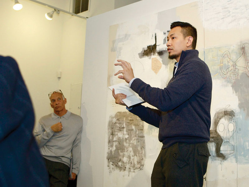 Artist Thomas Dang Vu speaking in front of artwork