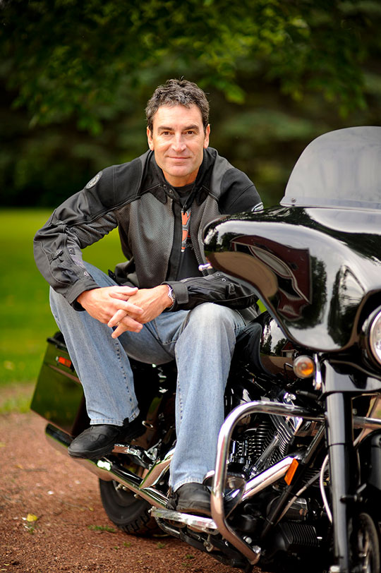 Ken Schmidt sitting on a Harley-Davidson motorcycle