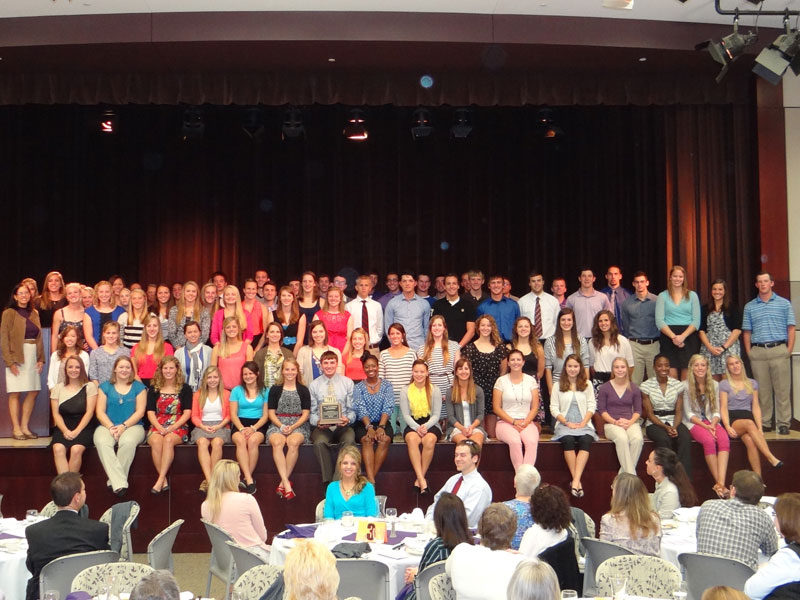Large group of student-athletes standing and sitting on stage