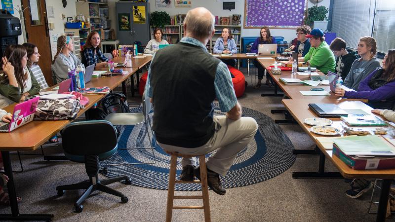 UE faculty member sitting in the center of a room on a stool giving course in classroom.