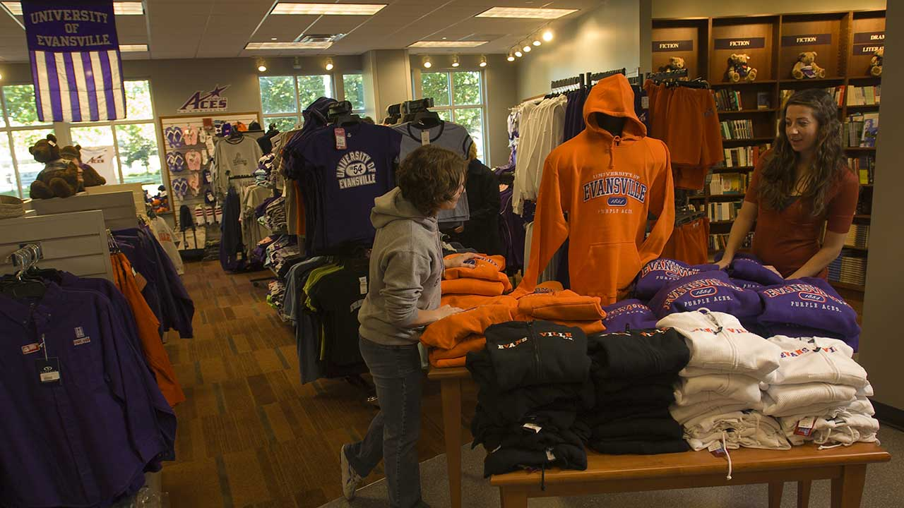 Students browsing UE themed hoodies in the University of Evansville Bookstore.