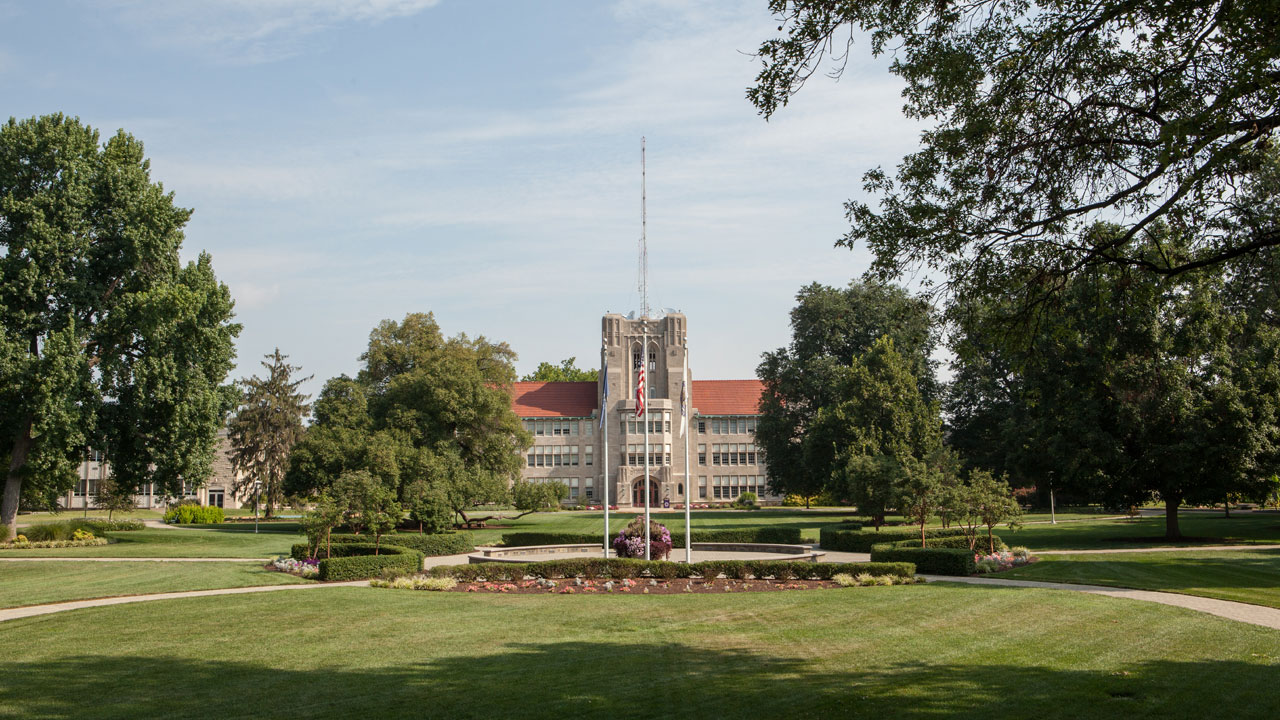 Flagpoles in front of Olmstead Administration Hall as seen from the campus oval.