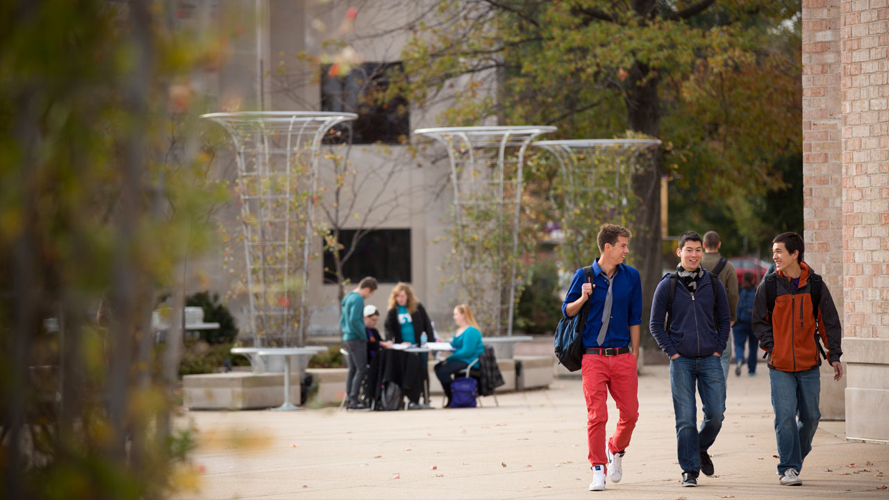 Three male students with backpacks walking in front of Ridgway University Center.