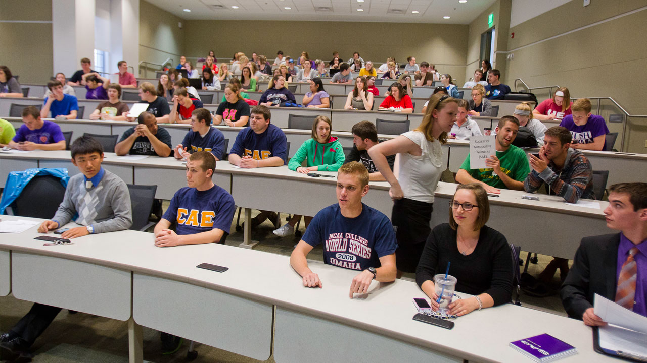 UE students prepair to listen to a lecture in an auditorium style classroom.