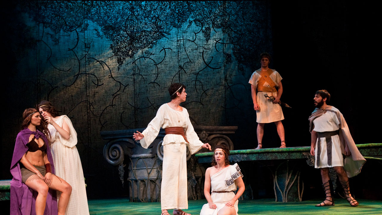 UE Theatre students on stage during a performance wearing ancient Greek themed costumes.